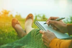 Young woman with notebook and pen outside.